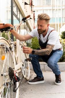 Nahaufnahme eines jungen mannes, der an einem fahrrad arbeitet Kostenlose Fotos
