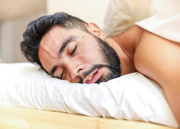 Nahaufnahme eines jungen mannes, der auf bett schläft