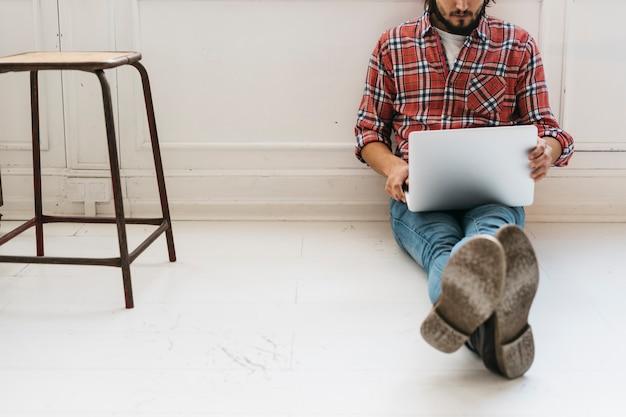 Nahaufnahme eines jungen mannes, der auf boden mit den gekreuzten beinen unter verwendung des laptops sitzt