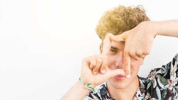 Nahaufnahme eines jungen mannes, der durch fingerrahmen schaut