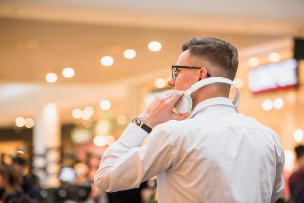 Nahaufnahme eines jungen mannes, der in der hand weißen kopfhörer hält