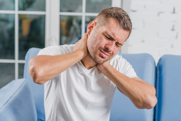 Nahaufnahme eines jungen mannes, der schmerz in seinem hals hat