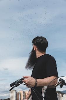 Nahaufnahme eines jungen mannes mit dem fahrrad, das menge der vögel fliegen in himmel betrachtet