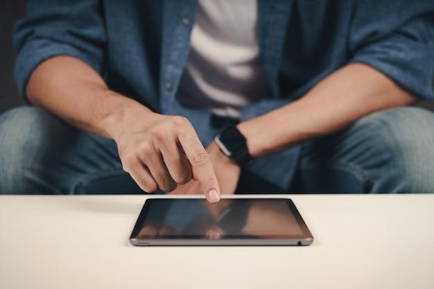 Nahaufnahme eines jungen mannes mit tablet auf dem sofa. suchen, surfen, online-shopping, soziales netzwerk.