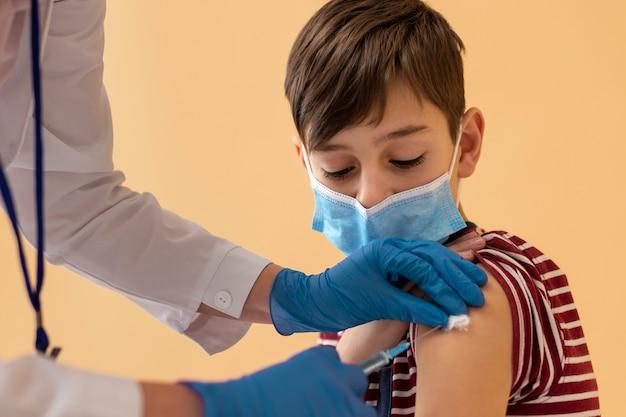 Nahaufnahme eines jungen mit maske, der einen impfstoff bekommt