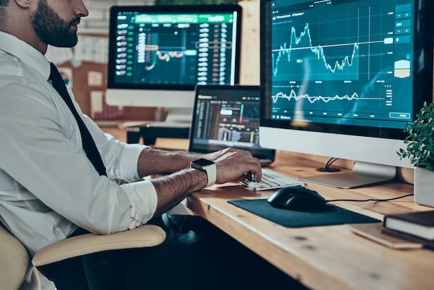 Nahaufnahme eines jungen modernen mannes in formeller kleidung, der mit computern arbeitet, während er im büro sitzt sitting