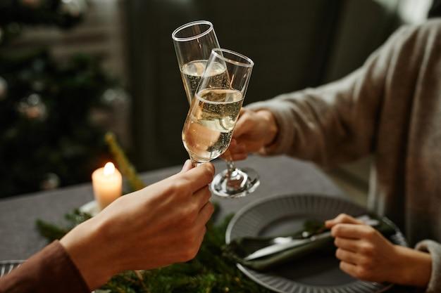 Nahaufnahme eines jungen paares, das zusammen weihnachtsessen genießt und mit sektgläsern anstößt, während...