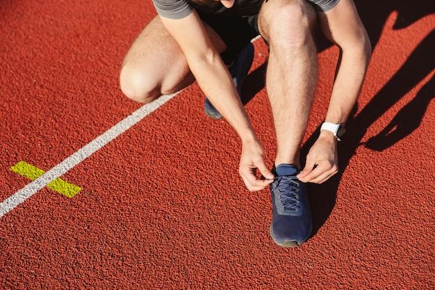 Nahaufnahme eines jungen sportlers, der schnürsenkel bindet
