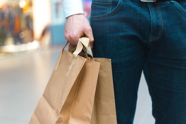 Nahaufnahme eines jungen stilvollen mannes, der in einem einkaufszentrum mit umweltfreundlichen einkaufstaschen in der hand mit waren und kleidung geht. verkauf, rabatt ausverkauftes konzept. saisonaler ausverkauf.