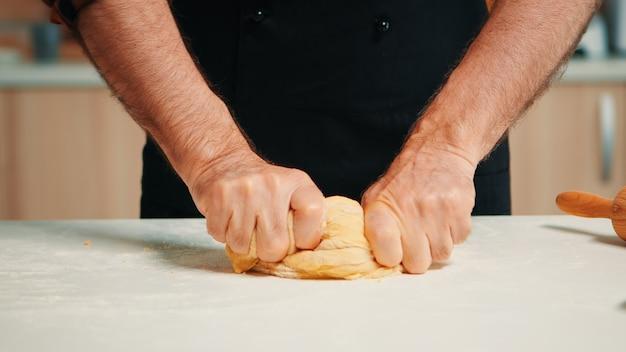 Nahaufnahme eines kaukasischen alten kochmannes, der ein brotlaib formt. pensionierter älterer bäcker mit küchenuniform, der zutaten mit gesiebtem weizenmehl knetet, um traditionellen kuchen und brot zu backen