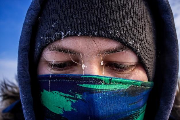 Nahaufnahme eines kaukasischen mannes gesicht mit schal als maske und kapuzen-winterjacke mit frost auf den augenbrauen