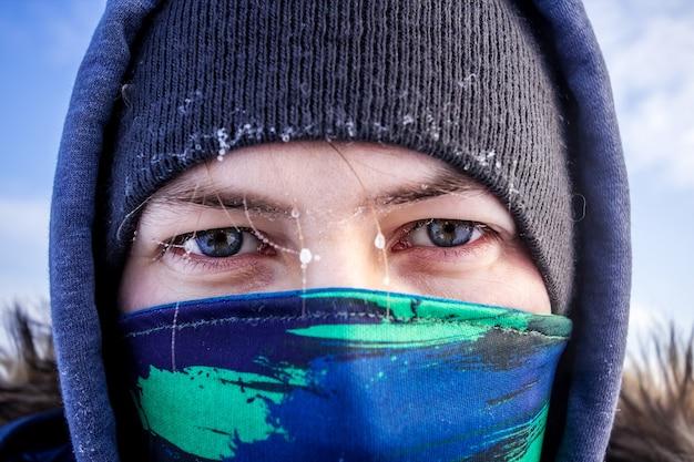 Nahaufnahme eines kaukasischen mannes gesicht mit schal und kapuzen-winterjacke mit frost auf den augenbrauen in die kamera schaut