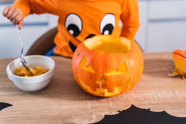 Nahaufnahme eines kindes, das als halloween-kürbis verkleidet ist und einen halloween-kürbis in seiner küche zu hause entleert
