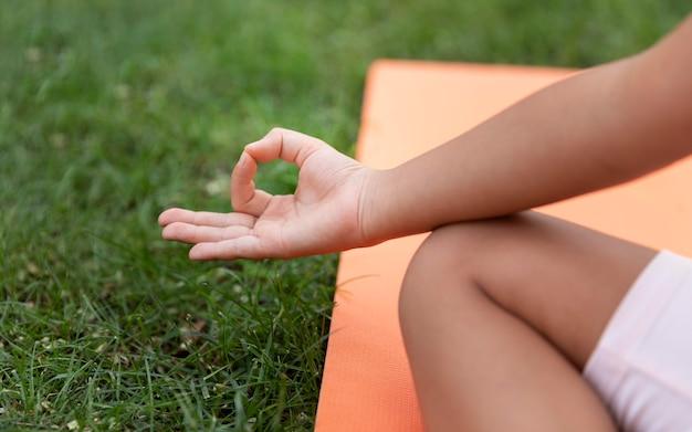 Nahaufnahme eines kindes, das draußen meditiert