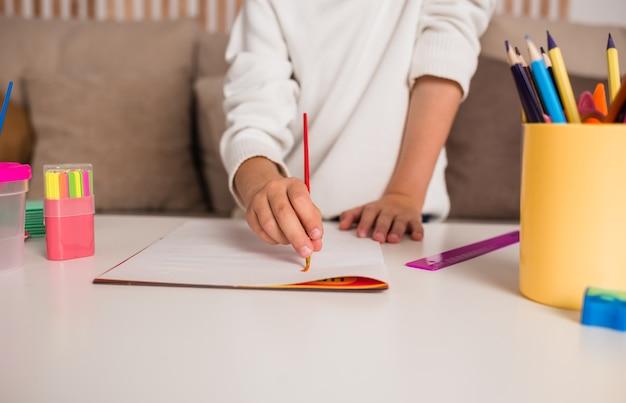 Nahaufnahme eines kindes, das mit einem pinsel in einem album auf einem tisch mit schulmaterial zeichnet