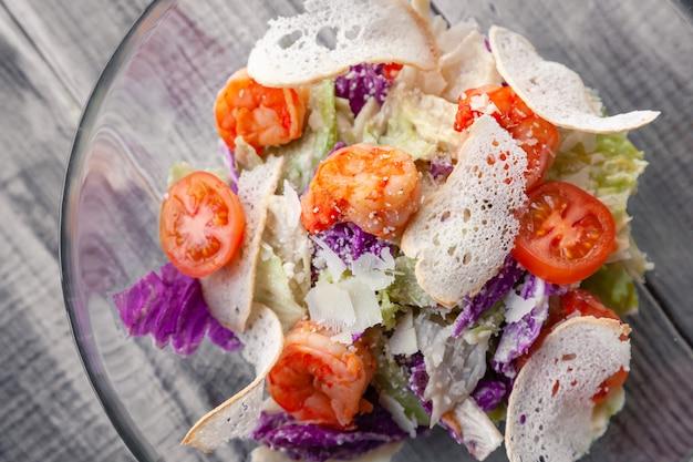 Nahaufnahme eines klassischen caesar-salats mit gegrillten garnelen, eisbergsalat, croutons, tomaten, chinakohl.