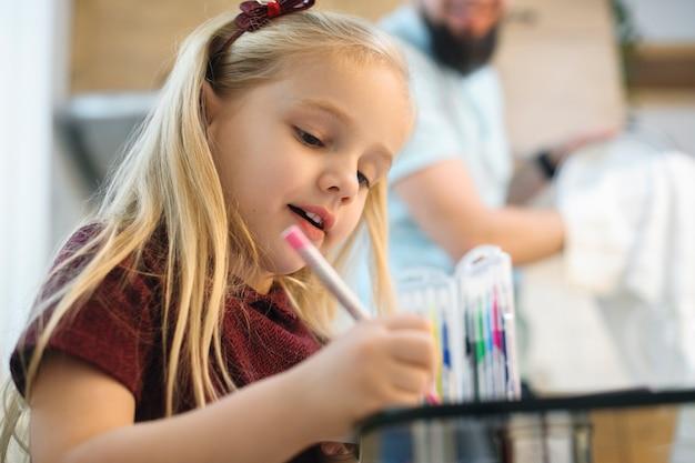 Nahaufnahme eines kleinen blonden mädchens, das in der küche spielt, während ihr vater geschirr spült und putzt.