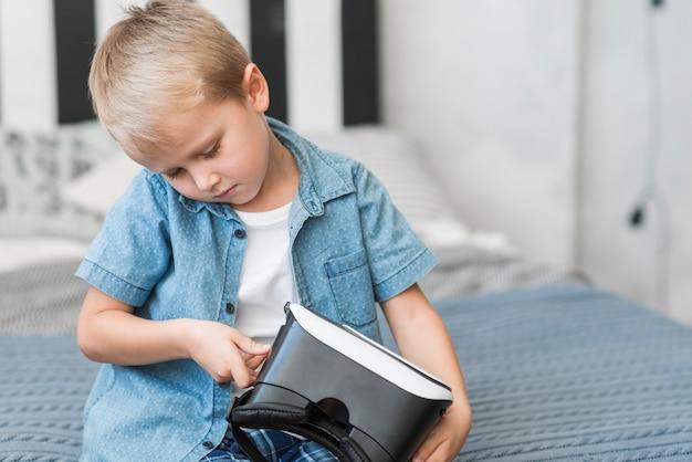 Nahaufnahme eines kleinen jungen, der auf dem bett justiert schutzbrillen der virtuellen realität sitzt