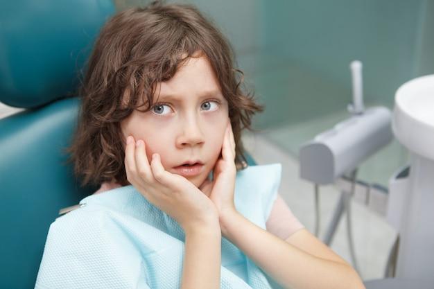 Nahaufnahme eines kleinen jungen, der verängstigt aussieht und im zahnarztstuhl sitzt