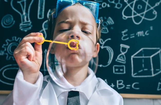 Nahaufnahme eines kleinen jungen wissenschaftlers, der mit seifenblasen gegen die gezeichnete tafel spielt?