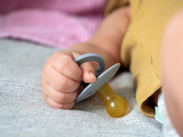 Nahaufnahme eines kleinen kindes, das einen schnuller mit der hand hält