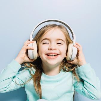 Nahaufnahme eines kleinen lächelnden mädchens, das die musik auf kopfhörer genießt
