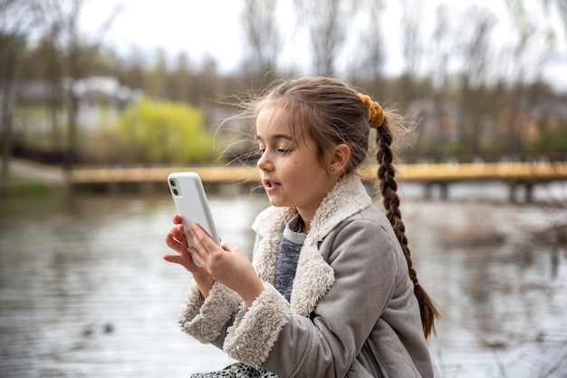 Nahaufnahme eines kleinen mädchens mit einem telefon in den händen auf dem hintergrund der natur.