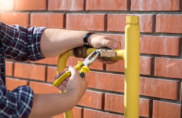 Nahaufnahme eines klempners, der ein neues ventil an einem gelben rohr außerhalb des hauses installiert