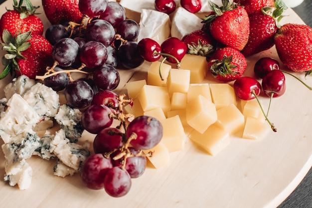 Nahaufnahme eines köstlichen essenstellers voller gewürzter frischer beeren, obst und käse.