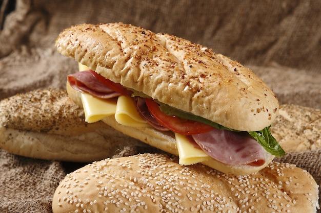 Nahaufnahme eines köstlichen sandwichs mit schinken, käse, tomaten und salat
