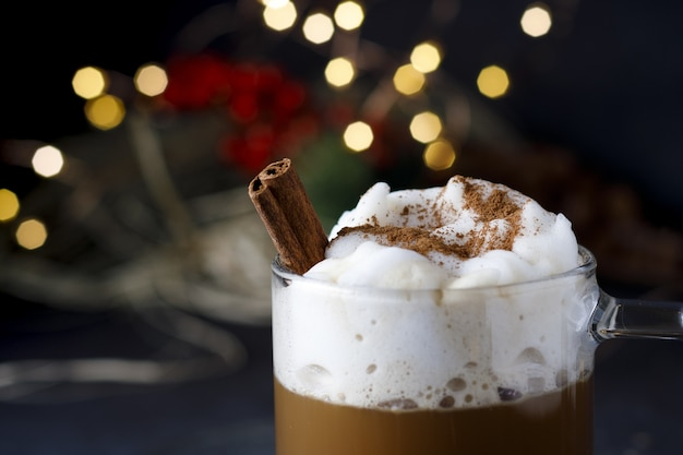 Nahaufnahme eines köstlichen weihnachtskaffees mit zimt und schaum, vor bokeh-lichtern
