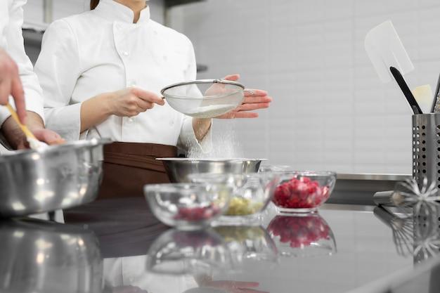 Nahaufnahme eines konditors übergibt einem mann und einer frau in einer professionellen küche einen biskuitkuchen zubereiten