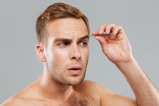 Nahaufnahme eines konzentrierten jungen mannes, der augenbrauenhaare mit einer pinzette entfernt