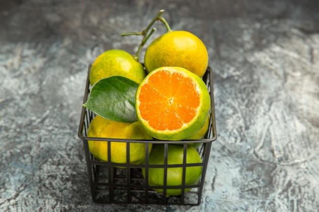 Nahaufnahme eines korbes voller frischer grüner mandarinen und halbierter mandarine auf grauem hintergrund