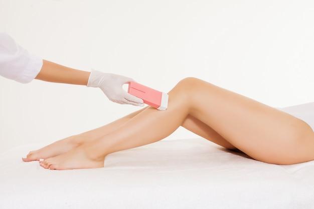 Nahaufnahme eines kosmetikers, der die beine der frau im schönheitsbadekurortsalon einwächst. depilation und haarentfernungskonzept.