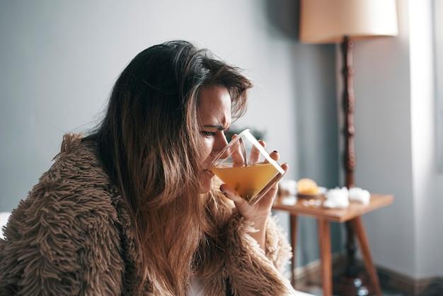 Nahaufnahme eines kranken mädchens, das ihre medizin im bett trinkt