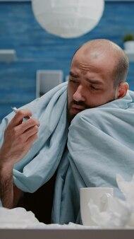 Nahaufnahme eines kranken mannes, der tablette und flasche mit pillen betrachtet