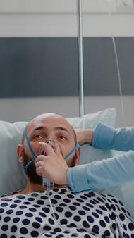 Nahaufnahme eines kranken patienten, der im bett ruht, während der arzt während eines notfalls im gesundheitswesen eine sauerstoffmaske aufsetzt, die atemwegserkrankungen in der krankenstation überwacht. arzt analysiert herzschlag pluse