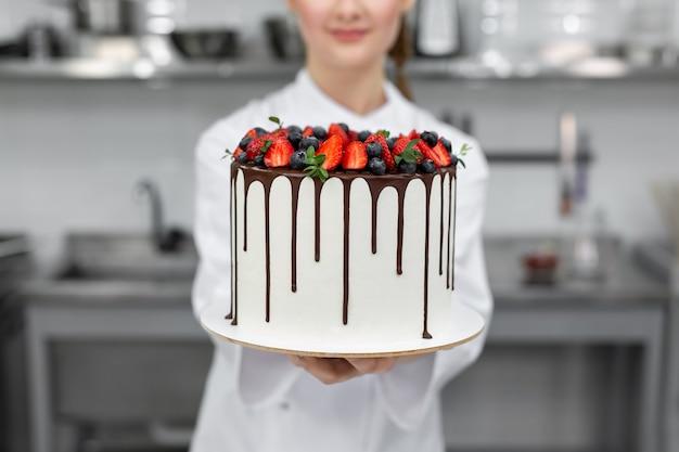 Nahaufnahme eines kuchens in den händen eines konditoren.