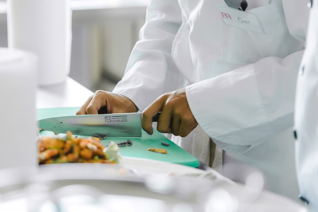 Nahaufnahme eines küchenchefs, der gemüse in lebensmittel schneidet in der küche kochen, um den kunden im hotelrestaurant essen zu servieren