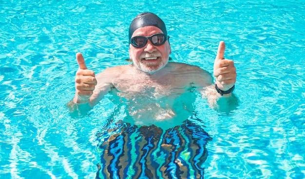 Nahaufnahme eines lächelnden älteren mannes, der sport macht und im schwimmbad schwimmt