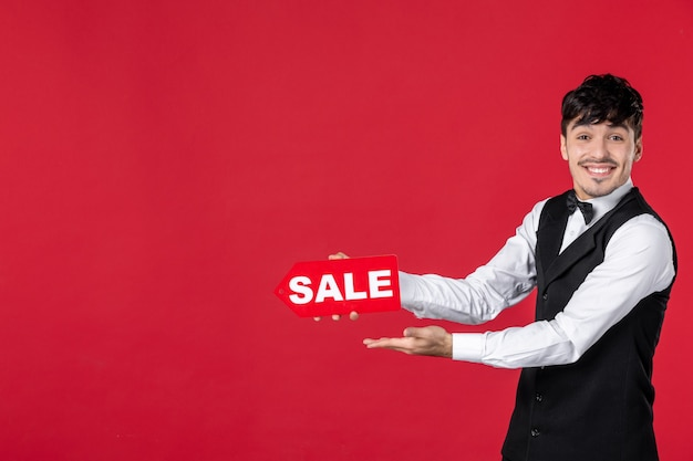 Nahaufnahme eines lächelnden, glücklichen kellners in uniform mit schmetterling am hals, der das verkaufssymbol zeigt, das auf etwas auf der rechten seite auf isoliertem rotem hintergrund zeigt