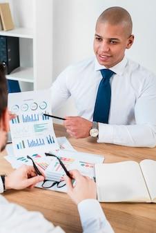 Nahaufnahme eines lächelnden jungen geschäftsmannes, der diagramm mit bleistift zu seinem teilhaber am arbeitsplatz zeigt