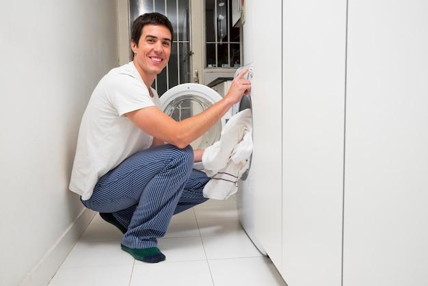 Nahaufnahme eines lächelnden jungen mannes, der kleidung in die waschmaschine einsetzt