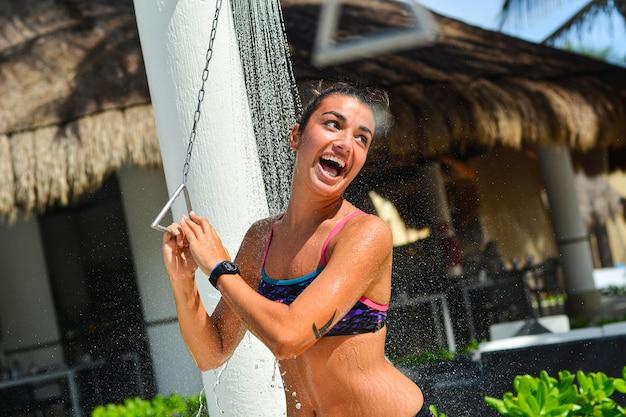 Nahaufnahme eines lächelnden mädchens, das am strand duscht?