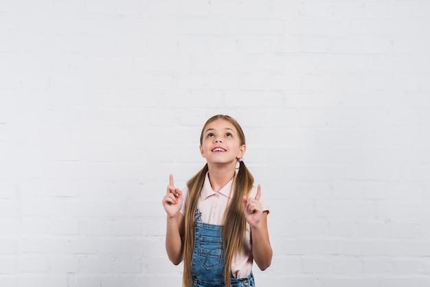 Nahaufnahme eines lächelnden mädchens, das den finger aufwärts schaut oben schaut gegen weiße backsteinmauer zeigt