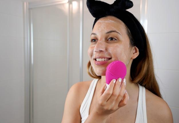 Nahaufnahme eines lächelnden mädchens, das die haut mit silikonbürsten-ultraschallmassage im badezimmer säubert