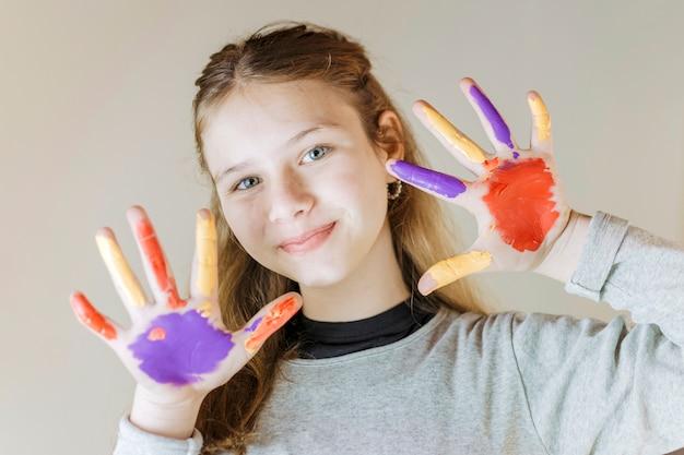 Nahaufnahme eines lächelnden mädchens mit den gemalten händen