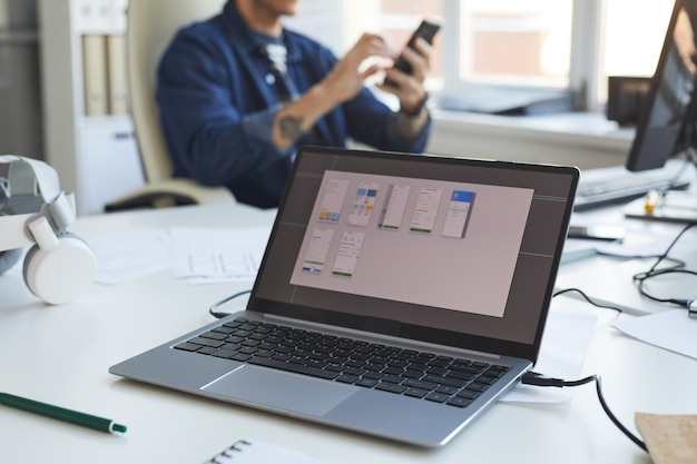 Nahaufnahme eines laptop-bildschirms mit software-design-planung mit it-entwicklungsteam im hintergrund, kopienraum