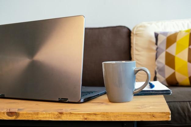 Nahaufnahme eines laptops, der auf einem tisch mit einer keramischen kaffeetasse und einem papiernotizblock sitzt. gemütlicher heimarbeitsplatz eines freiberuflers, fernarbeit von zu hause aus.